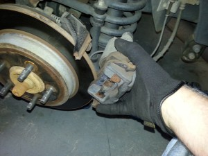 Tip the top of the caliper out first, then the bottom.  This will be reversed for installing after pads are replaced.